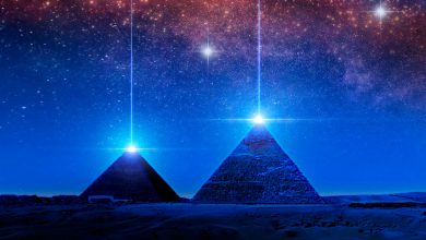 Pyramids and light above the night sky. Shutterstock.