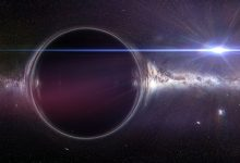 An artists rendering of a black hole with a gravitational lens effect and the Milky Way galaxy. Shutterstock.
