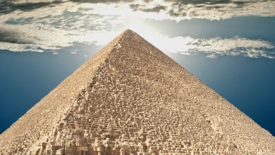The Great Pyramid of Giza and people climbing its supermassvie stones. Shutterstock.