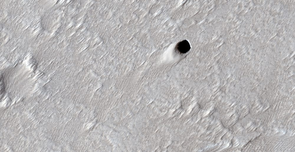 An image of the massive lava tube measuring approximately fifty meters in diameter photographed by the MRO as it flew over the Arsia Mons region on Mars. Image Credit: NASA/JPL/UArizona.