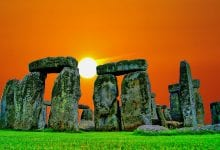 An image of the sun setting behind the stones of Stonehenge. Jumpstory.