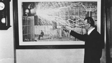 Nikola Tesla standing in front of one of his most famous photographs.