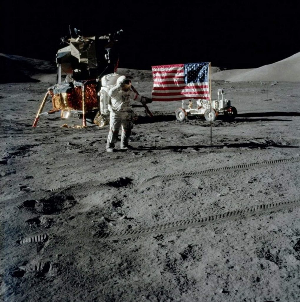 An image of Apollo 17 Commander Gene Cernan with the American flag during Apollo 17. Credit: Smithsonian National Air and Space Museum / NASA