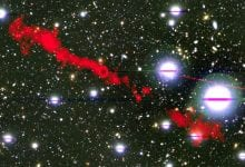In this image, you can see one of the giant radio galaxies (MGTC J100016.84+015133.0) in red and a cosmic background as you would see it in optical light. Credit: I. Heywood, University of Oxford / Rhodes University / South African Radio Astronomy Observatory / CC BY 4.0.