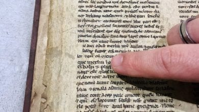 A researcher points to the name of Merlin in the 13th century manuscript. Credit: University of Bristol