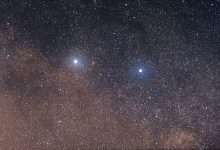 The two bright stars are (left) Alpha Centauri and (right) Beta Centauri. The faint red star in the center of the red circle is Proxima Centauri. Taken with Canon 85mm f/1.8 lens with 11 frames stacked, each frame exposed 30 seconds. Image Credit: Skatebiker / Wikimedia Commons.