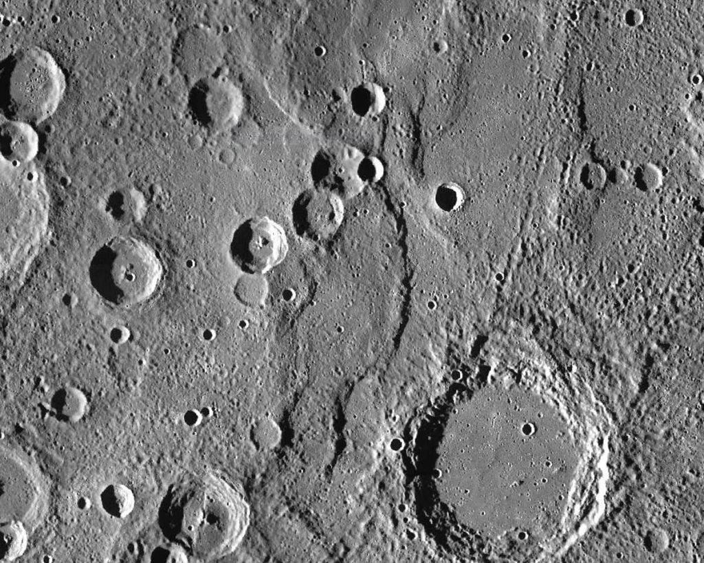 Endeavour Rupes, the shadowed escarpment in the middle of a 400km wide view of Mercury. Image Credit: NASA/JHUAPL/CIW.