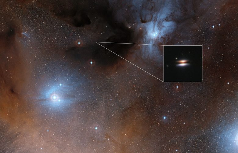 The young star 2MASS J16281370-2431391 lies in the spectacular Rho Ophiuchi star formation region, about 400 light-years from Earth. It is surrounded by a disc of gas and dust — such discs are called protoplanetary discs as they are the early stages in the creation of planetary systems. This particular disc is seen nearly edge-on, and its appearance in visible light pictures has led to its being nicknamed the Flying Saucer. The main image shows part of the Rho Ophiuchi region and a much enlarged close-up infrared view of the Flying Saucer from the NASA/ESA Hubble Space Telescope is shown as an insert. Image Credit: Wikimedia Commons.