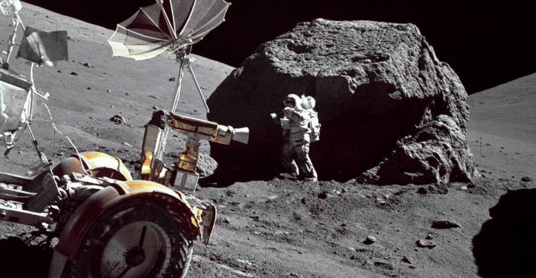 "Geologist-Astronaut Harrison H. Schmitt is photographed standing next to a huge, split boulder at Station 6 on the sloping base of North Massif during the third Apollo 17 extravehicular activity (EVA-3) at the Taurus-Littrow landing site. The ""Rover"" Lunar Roving Vehicle (LRV) is in the left foreground. Schmitt is the Apollo 17 Lunar Module pilot. This picture was taken by Commander Eugene A. Cernan on n December 13, 1972. Image Credit: NASA."