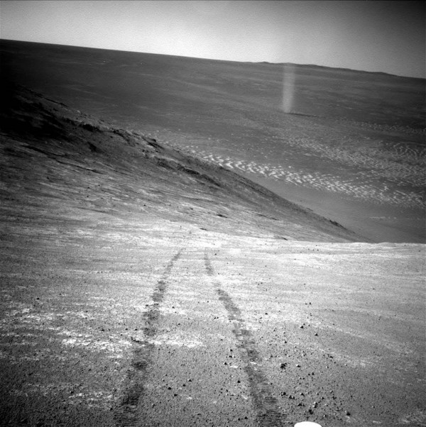 View larger. | From high on a ridge, NASA's Mars rover Opportunity recorded this image of a swirling Martian dust devil on March 31. Image via NASA/JPL-Caltech.