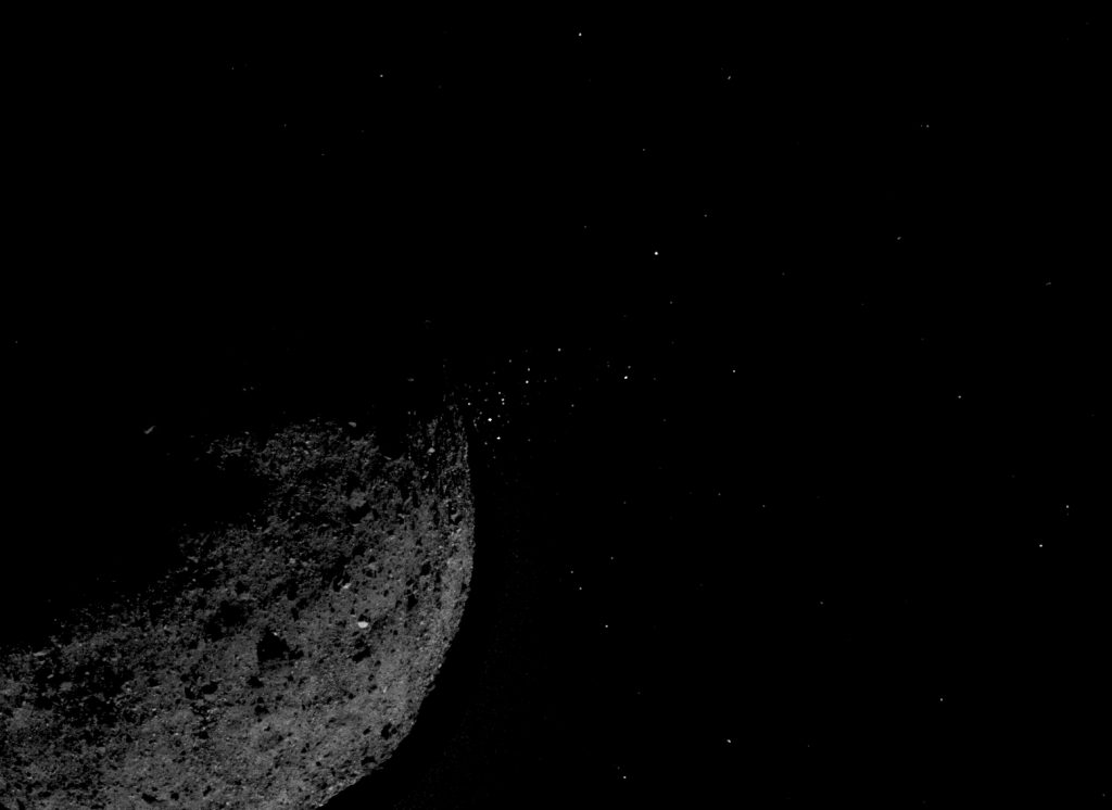 This view of asteroid Bennu ejecting particles from its surface on January 19 was created by combining two images taken by the NavCam 1 imager onboard NASA's OSIRIS-REx spacecraft: a short exposure image (1.4 ms), which shows the asteroid clearly, and a long exposure image (5 sec), which shows the particles clearly. Other image processing techniques were also applied, such as cropping and adjusting the brightness and contrast of each layer. Image Credit: NASA/Goddard/University of Arizona/Lockheed Martin.