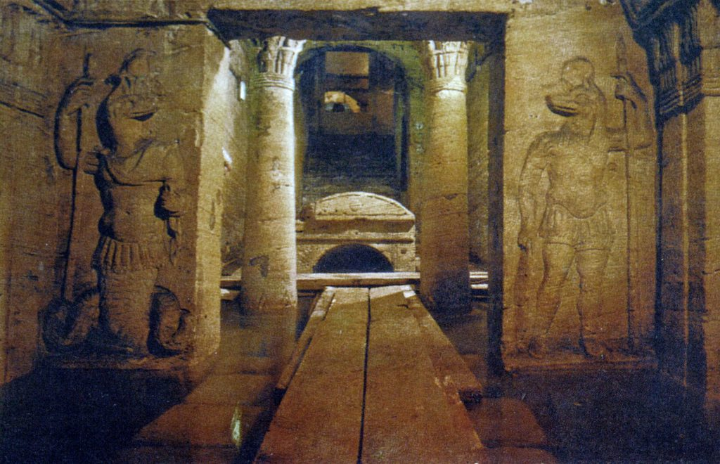 A view of the entrance to a burial chamber flanked by Ancient Egyptian Gods. Image Credit: Wikimedia Commons.