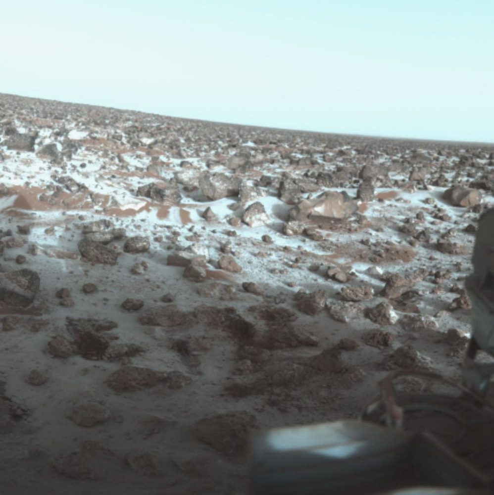 This photo shows the surface of Mars and was taken by Viking Lander 2 at its Utopia Planitia landing site on May 18, 1979, and relayed to Earth by Orbiter 1 on June 7. It shows a thin coating of water ice on the rocks and soil. Image Credit: NASA / Wikimedia Commons.