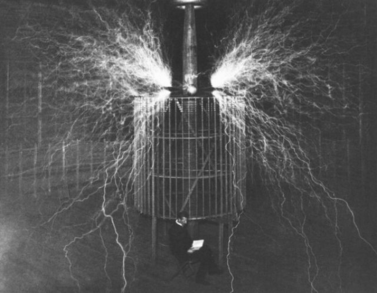 A photograph of Nikola Tesla sitting in front of his generator. The image was taken around 1899.