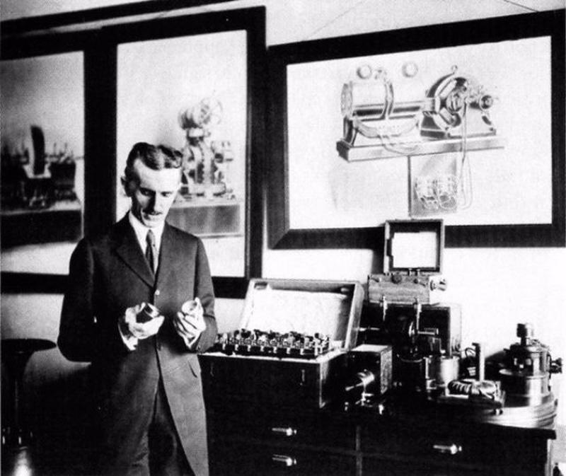 A photograph of Nikola Tesla standing in his New York City Office in 1916.