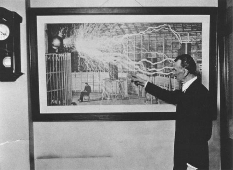 Nikola Tesla in 1916 pointing towards a photograph captured in Colorado Springs in 1899.