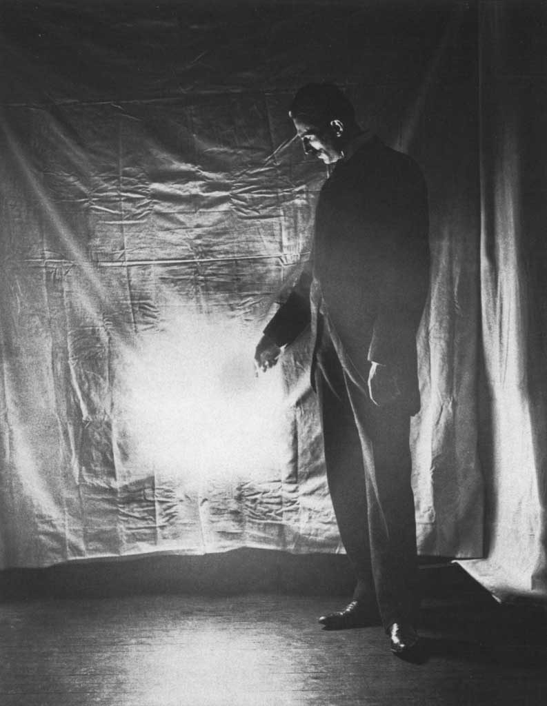 Nikola Tesla photographed in 1898 demonstrating wireless energy transmission.