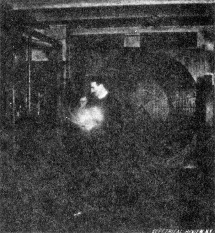 An image of Nikola Tesla lighting a vacuum bulb using waves originating from a distant oscillator.