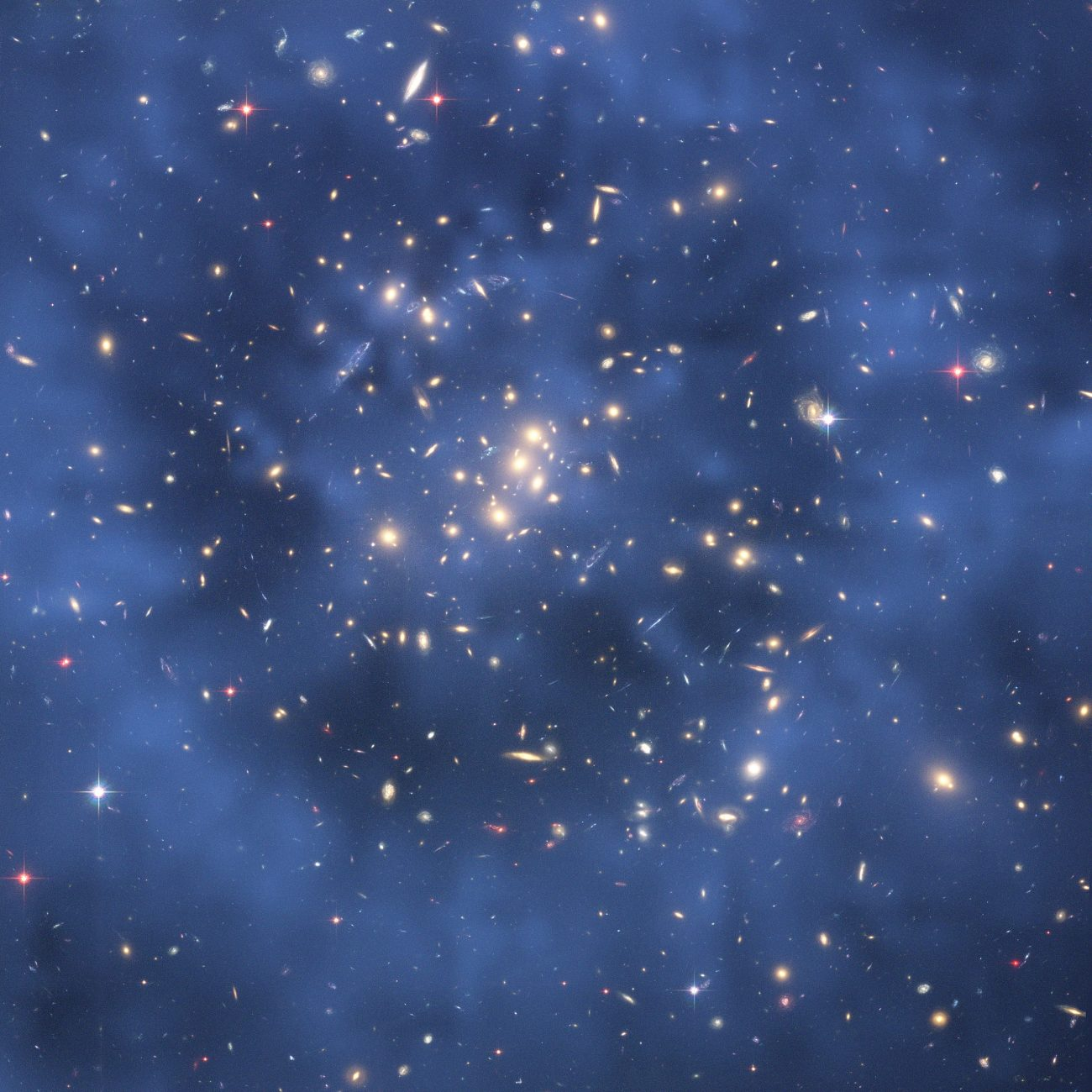 Composite image of the cluster of galaxies CL0024 + 17 taken by the Hubble Space Telescope shows the creation of a gravitational lens effect. It is assumed that this effect is due, in large part, to the gravitational interaction with dark matter. Image Credit: Wikimedia Commons.