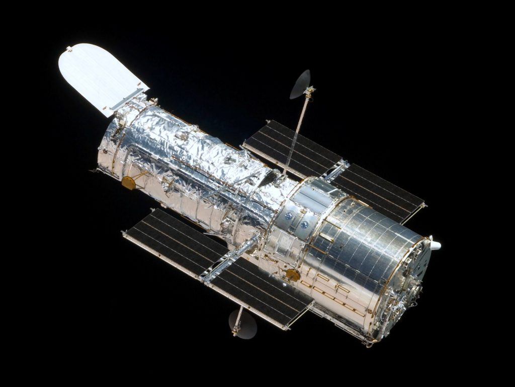 The Hubble Space Telescope in orbit as seen from the departing Space Shuttle Atlantis, flying Servicing Mission 4 (STS-125), the fifth and final Hubble mission. Image Credit: Wikimedia Commons.