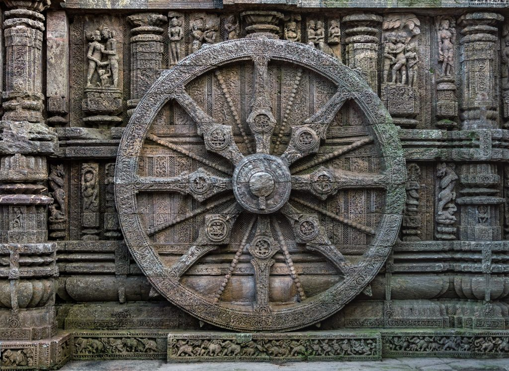 A stone wheel engraved in the walls of the temple. The temple is designed as a chariot consisting of 24 such wheels. Each wheel has a diameter of 9 feet, 9 inches, with 8 spokes. Image Credit: Wikimedia Commons.