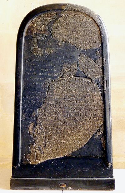 The Mesha Stele in its current location: The brown fragments are pieces of the original stele, whereas the smoother black material is Ganneau's reconstruction from the 1870s. Image Credit: Wikimedia Commons.