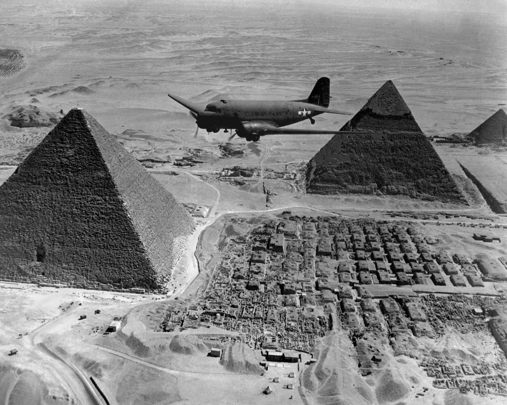 American Air Transport Command plane flies over the pyramids of Egypt. Flights from the U.S. supplied strategic battle zones of North Africa during World War 2. 1943. Shutterstock.