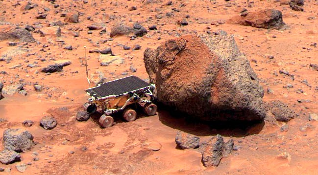 Sojourner takes Alpha Proton X-ray Spectrometer measurements of the Yogi Rock. Image Credit: Wikimedia Commons.