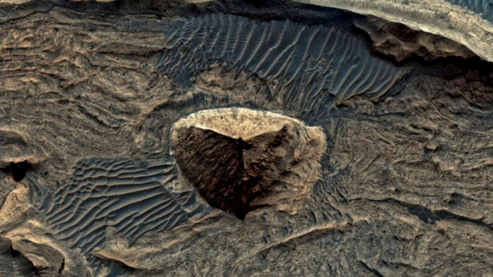 A hill on Mars. The pyramid shape is due to erosion.