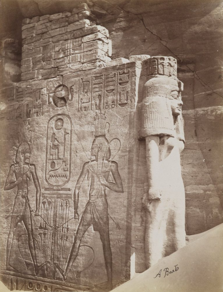 Queen Nefetari at Temple of Abu Simbel (View of detail of throne and queen below the seated Colossus of Ramsses II at the north side of the entrance to the South Temple). Image Credit: Brooklyn Museum / Public Domain.