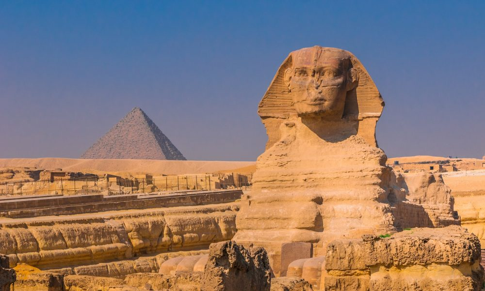 Frontal view of the Sphinx with the pyramid in the background. Shutterstock.
