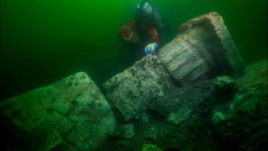 Underwater explorer next to the collumn of a sunken temple. Image Credit: Christoph Gerigk, Franck Goddio / Hilti Foundation.