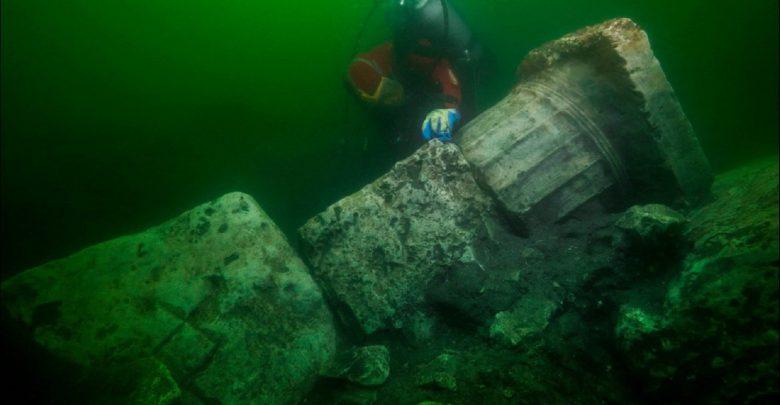 Underwater explorer next to the collumn of a sunken temple. Image Credit: Christoph Gerigk, Franck Goddio / Hilti Foundation.