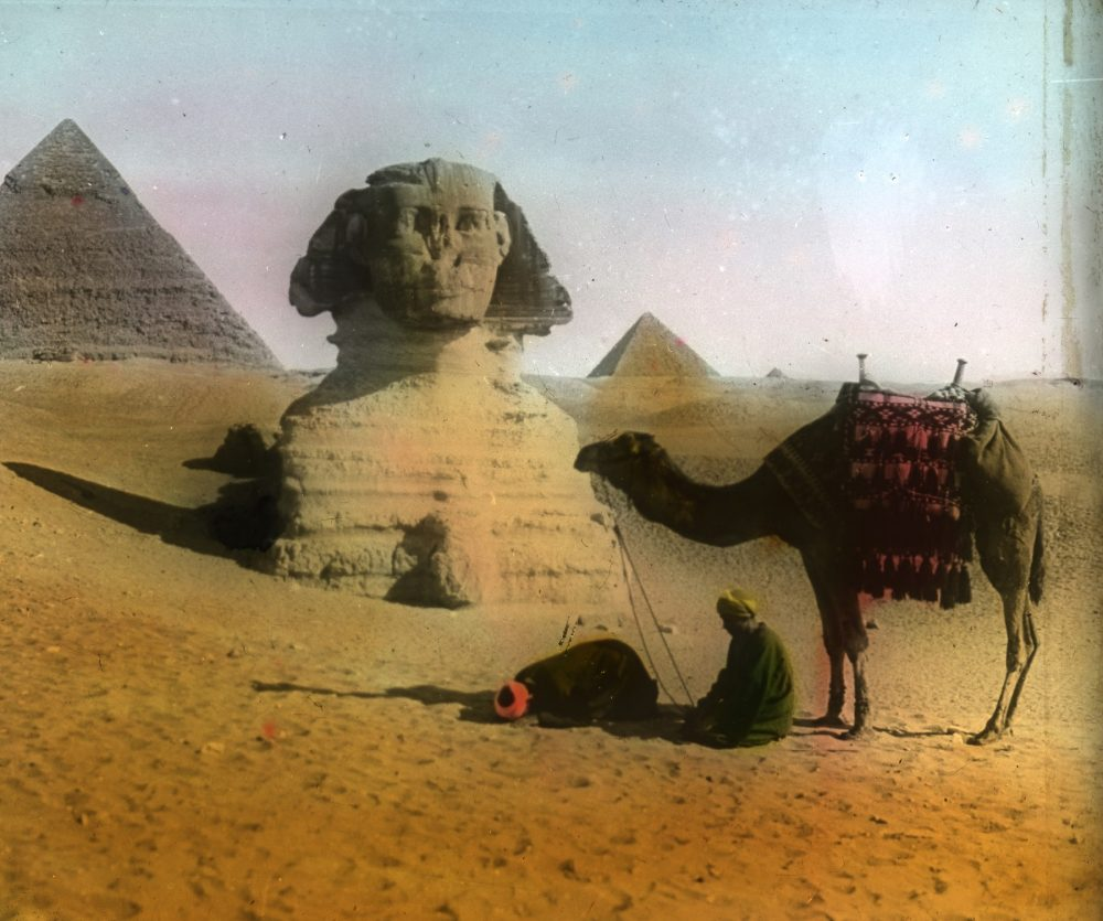 The Sphinx buried in sand with the Pyramids in the background. Image Credit: Wikimedia Commons.