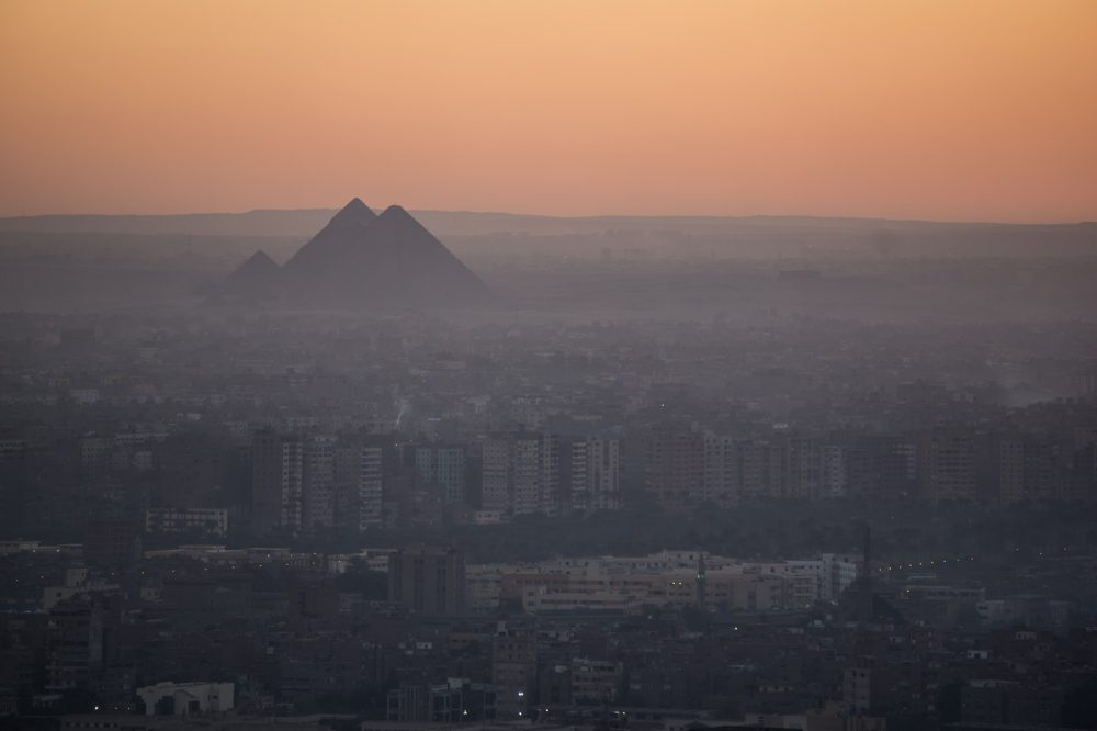 The pyramids of Giza in the background, surrounded by a jungle of modern buildings. Shutterstock.