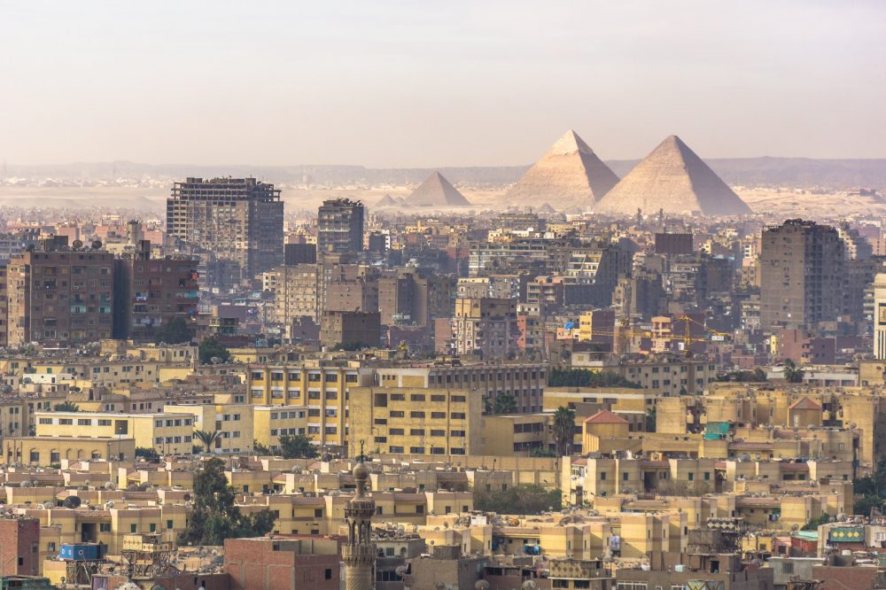 Modern buildings have almost invaded the Giza pyramids. Shutterstock.