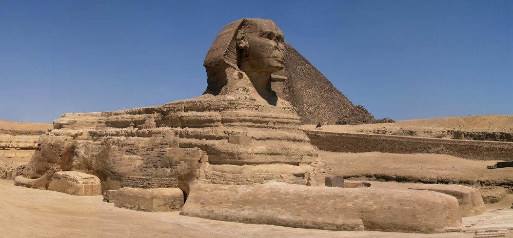 A wide panoramic view of the Great Sphinx with Great Pyramid of Khufu in background. Shutterstock.