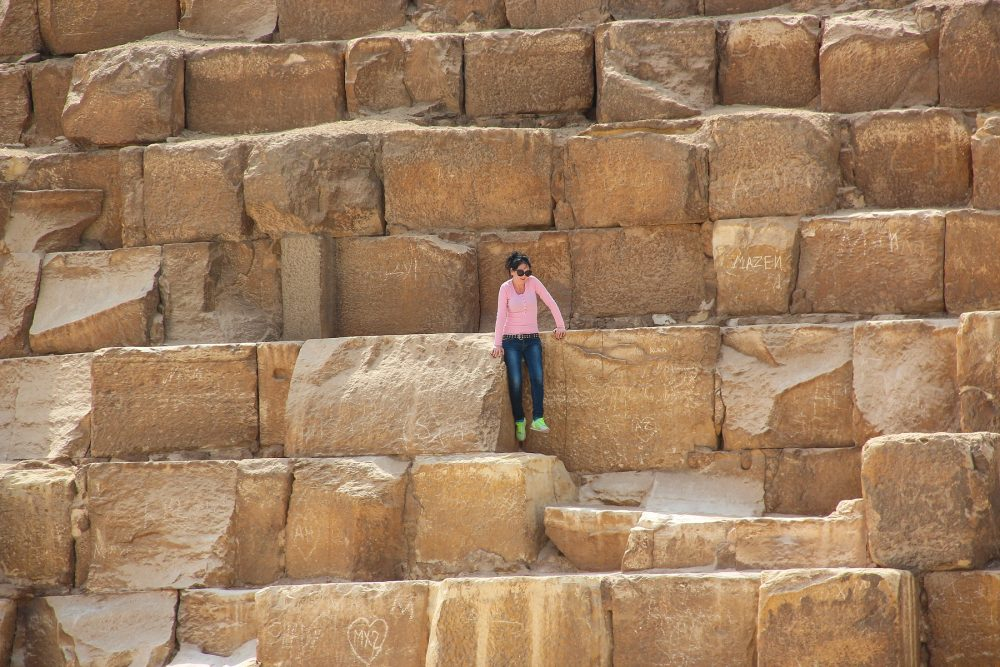 A woman sitting on the blocks of the Great Pyramid at Giza. Shutterstock.
