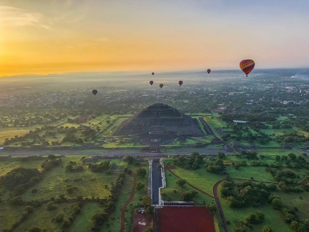 Beautiful aerial view of the Pyramids of Teotihuacan Mexico with balloons in the sunset. Shutterstock.
