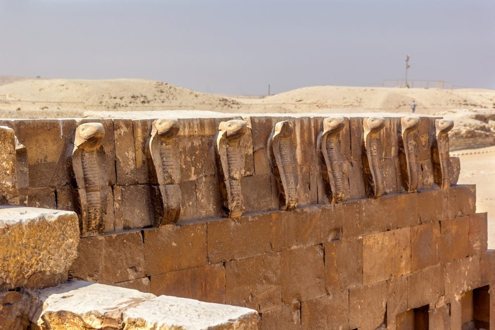 The intricately carved cobras at Saqqara. Shutterstock.