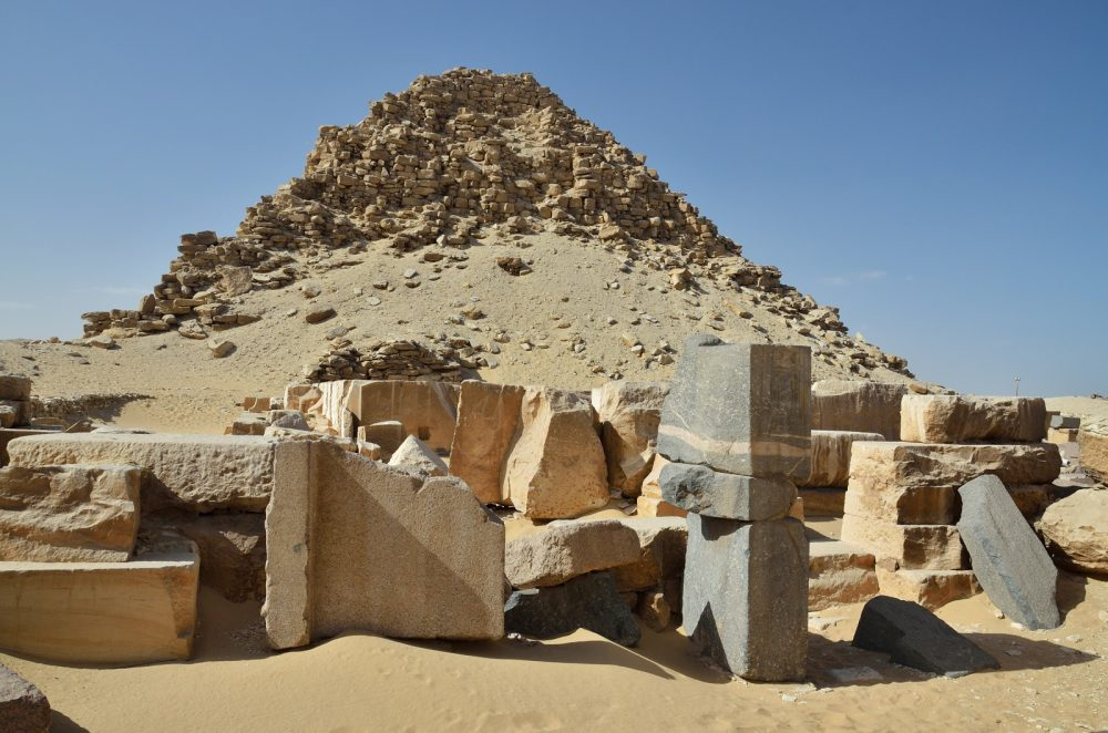 Seen here are massive stones and the pyramid of Sahure in the background. Shutterstock.
