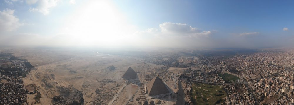 The pyramids of Giza with the sun shining brightly in the background. Shutterstock.