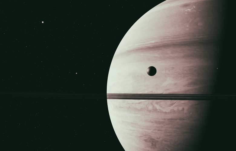 Saturn along with its moon rhea, close up 3D rendering. Shutterstock.
