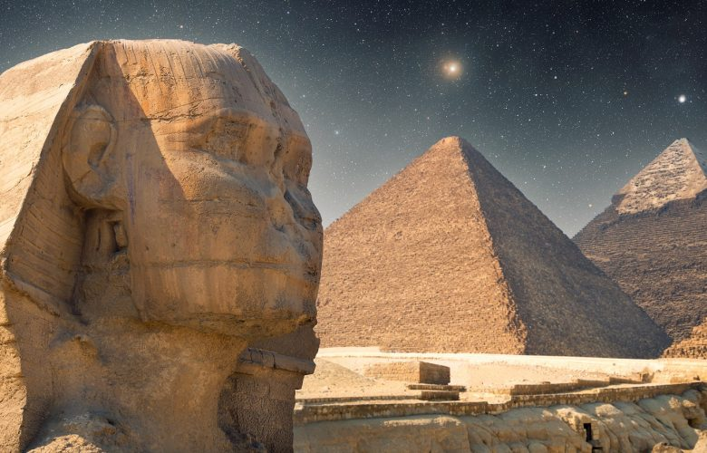 An image showing the The Sphinx, the Great Pyramid and Khafre's Pyramid with the night sky in the background. Shutterstock.