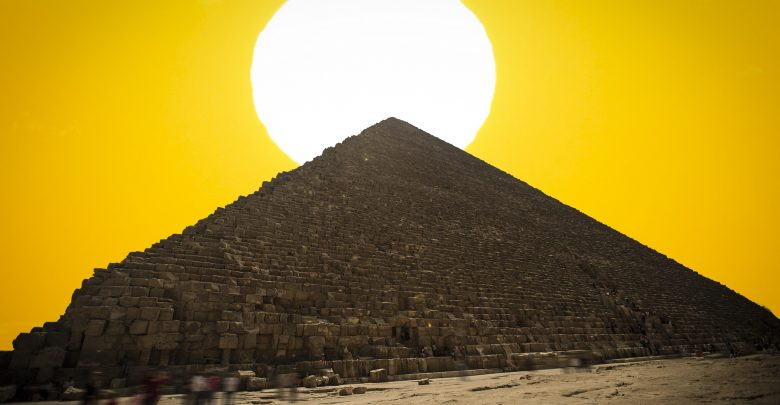 An image of the Great Pyramid of Giza with the Sun in the background. Shutterstock.