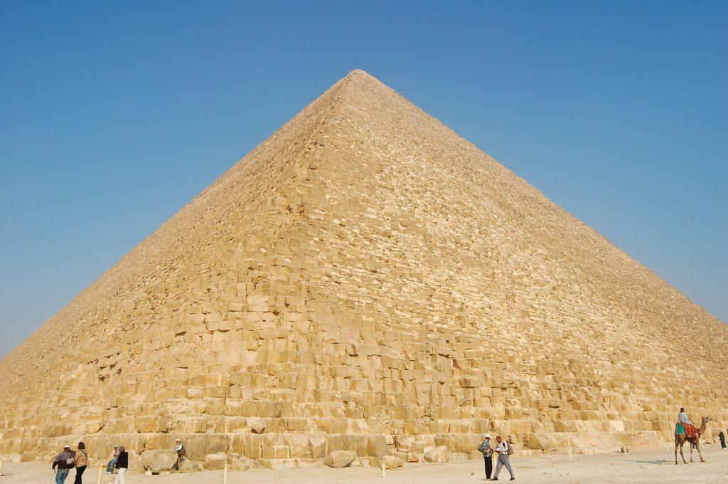 People standing in front of the Great Pyramid at Giza. Shutterstock.