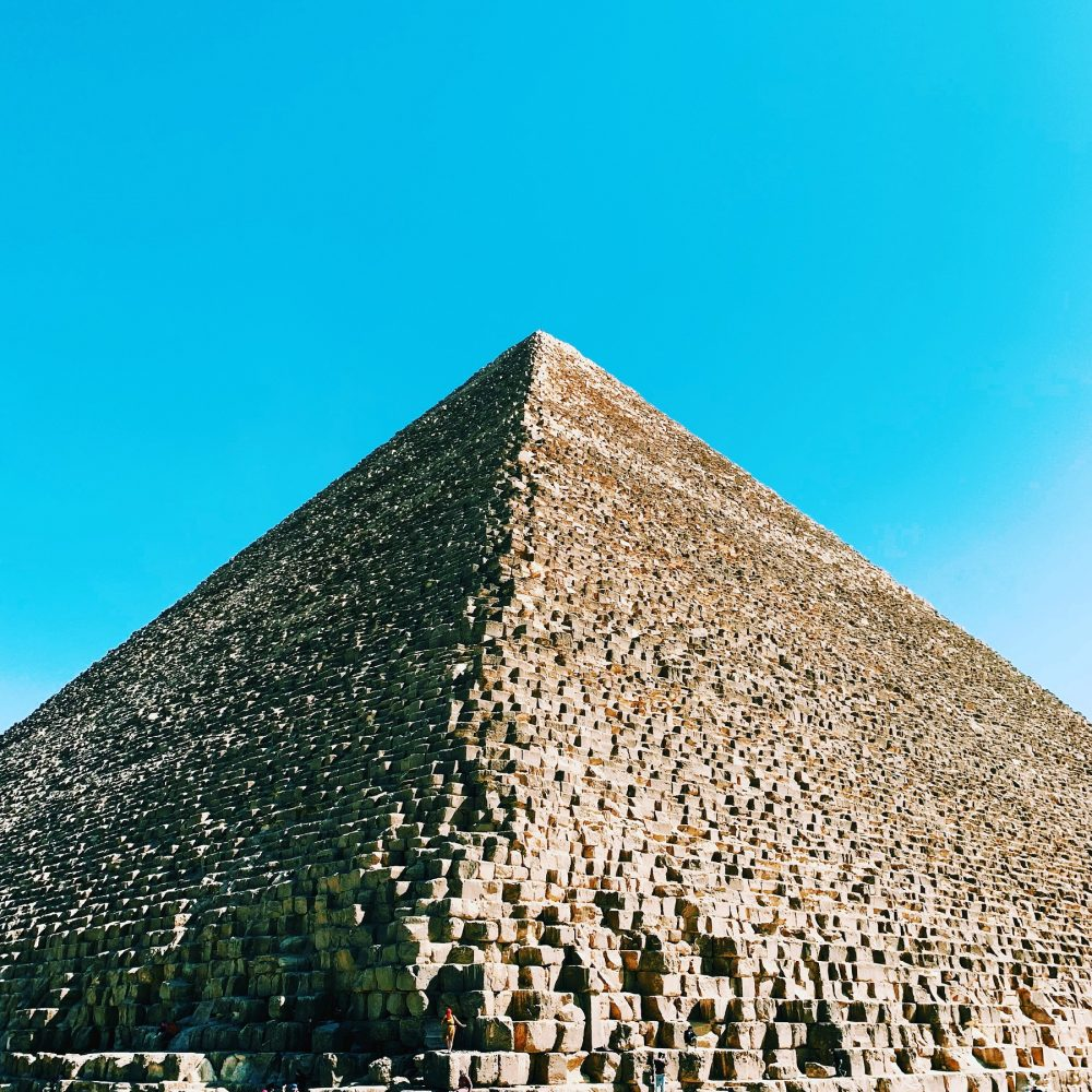 An image of the Great Pyramid of Giza and a person standing on one of the massive stones at its base. Shutterstock.