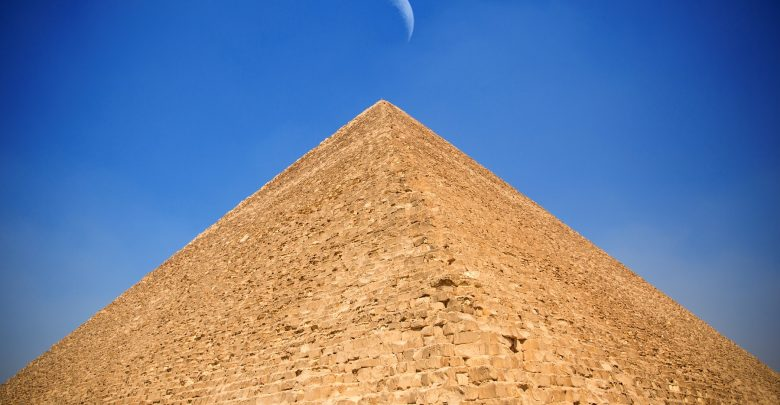 The Great Pyramid of Giza and the moon hovering above its summit. Shutterstock.