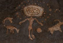 An image of cave art depicting a humanoid with spheres and depictions of what may be animals. Shutterstock.