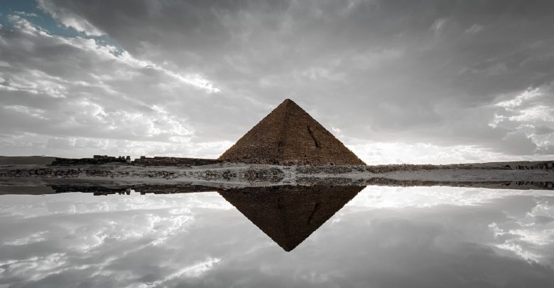 An image of an ancient Egyptian pyramid and its reflection. Shutterstock.